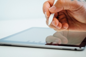 Hand holding white stylus pen above a black tablet device. There is a white background and the hand is about to draw.